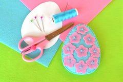 Huevo de Pascua del fieltro con las flores Tijeras, hilo, aguja, pernos, plantillas de papel Macro Artes hechos a mano Fotografía de archivo