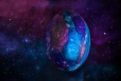 Huevo de Pascua en estilo del espacio Huevo de Pascua en estilo del espacio en el fondo del cielo estrellado y de la galaxia foto de archivo libre de regalías