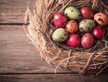 Huevo de Pascua en jerarquía en fondo de madera rústico Foto de archivo