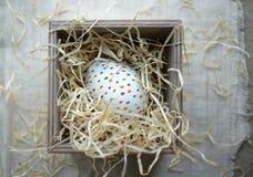 Huevo de Pascua en una caja con el heno Abigarrado coloreó el huevo en una mota foto de archivo