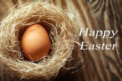 Huevo de Pascua feliz en la jerarquía en fondo de madera Foto de archivo