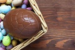 Huevo de Pascua grande del chocolate en una cesta Foto de archivo