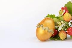 Huevo de Pascua de oro con el espacio en el fondo blanco Imagen de archivo libre de regalías