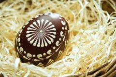 Huevo de Pascua pintado en una cesta con la paja, fondo de pascua Imagenes de archivo
