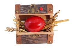 Huevo de Pascua rojo en el rectángulo del tesoro Imagen de archivo libre de regalías