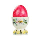 Huevo de Pascua rojo en un tenedor de la porcelana aislado en el fondo blanco Foto de archivo