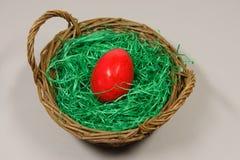 Huevo de Pascua rojo en una cesta Fotos de archivo libres de regalías