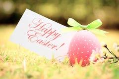 Huevo de Pascua rosado en hierba con la tarjeta verde del arco-nudo y de felicitación Imagen de archivo