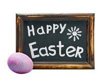 Huevo de Pascua y saludos de Pascua en una pizarra Fotos de archivo