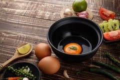 huevo del foco selectivo en cuenco e ingredientes en el fondo de madera Imagen de archivo