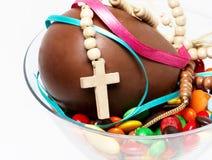 Huevo, dulces y cruz de chocolate de Pascua en un vidrio Foto de archivo libre de regalías