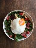 Huevo escalfado con tocino ahumado, ensalada, queso y pan para el desayuno foto de archivo