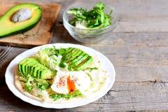 Huevo escalfado del desayuno sano del huevo, rebanadas de aguacate, col, mezcla de la lechuga, tortilla, salsa y especias Fotos de archivo libres de regalías