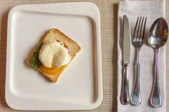 Huevo escalfado, en una rebanada tostada de pan blanco con el tomate y el condimento en una placa blanca de la porcelana imagen de archivo libre de regalías