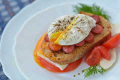 Huevo escalfado hervido, delicioso en el bocadillo, adornado con queso, tomate, hierbas en el fondo blanco de la placa Imágenes de archivo libres de regalías