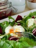 Huevo escalfado Open en una ensalada verde y pedazos de remolachas Fotografía de archivo libre de regalías