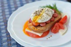 Huevo escalfado sabroso y condimentado en el bocadillo con la carne, queso, tomate en la placa blanca Imagen de archivo