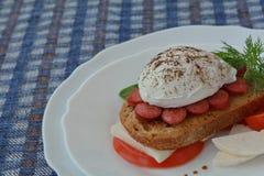 Huevo escalfado, salchicha, pan, queso feta, tomate en fondo azul de la servilleta Fotos de archivo