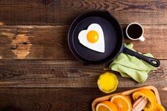 Huevo frito de la forma del corazón, zumo de naranja fresco y café Visión superior Imágenes de archivo libres de regalías