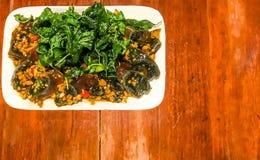 Huevo frito del mil-año con las hojas santas curruscantes de la albahaca y plato del arroz en un fondo de madera de la tabla con  Imagenes de archivo