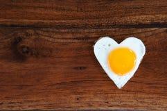 Huevo frito en forma de corazón en fondo de madera Imagenes de archivo