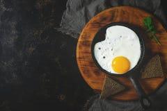 Huevo frito en la cacerola Fondo oscuro, espacio de la copia Foto entonada imagen de archivo libre de regalías