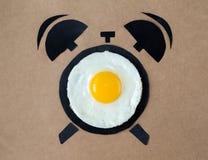 Huevo frito en la forma del despertador, concepto del tiempo de desayuno Imagen de archivo