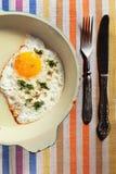 Huevo frito natural en un sartén viejo con un cuchillo viejo y para Imágenes de archivo libres de regalías