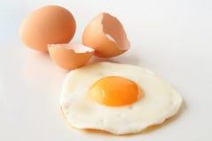Huevo frito tradicional con el shell agrietado y el huevo entero Imagenes de archivo
