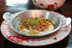 Huevo frito y salchicha de cerdo blanca cortada en cacerola caliente Imagen de archivo libre de regalías