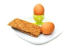 Huevo hervido en un soporte verde y un pan blanco. Imagen de archivo libre de regalías