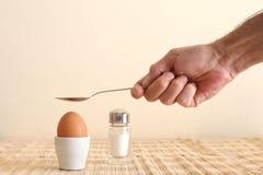 Huevo hervido en una huevera y una mano del ` s del hombre que sostienen una cuchara imagen de archivo