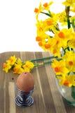 Huevo, huevera y narcisos. Imagen de archivo