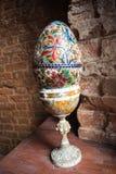 Huevo pintado grande en un soporte en un fondo del ladrillo rojo imágenes de archivo libres de regalías