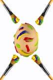 Huevo pintado movimientos multicolores con los cepillos alrededor Fotografía de archivo