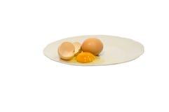Huevo quebrado aislado en una placa blanca Imágenes de archivo libres de regalías
