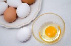 Huevo quebrado del pollo y huevos blancos y marrones en la placa Fotos de archivo libres de regalías