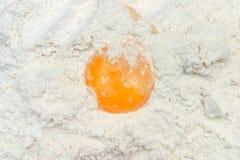 Huevo quebrado en la harina Foto de archivo