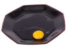 Huevo quebrado en la placa negra Fotografía de archivo libre de regalías