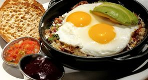 Huevo Ranchero Egg Skillet Salsa Avacado English Muffin. Huevo Ranchero Egg Skillet with Salsa, Avacado slices, sunny side up eggs over sauteed vegetables with a royalty free stock photo