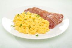 Desayuno del huevo revuelto y del tocino imagenes de archivo