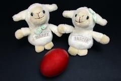 Huevo rojo blanco de dos ovejas felices decorativas de pascua Imagen de archivo libre de regalías