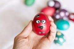 Huevo rojo moderno de pascua en una mano imagen de archivo