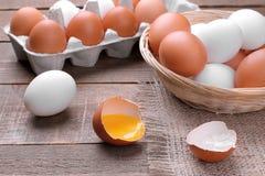 Huevo tajado del pollo con el primer de la yema de huevo al lado de los huevos en cesta y bandeja en fondo marrón foto de archivo libre de regalías