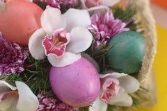 Huevo verde anaranjado púrpura entre las flores en cesta Foto de archivo