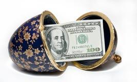 Huevo y $ 100 Fotos de archivo libres de regalías