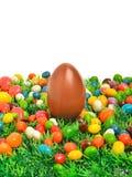 Huevo y caramelos de chocolate de Pascua en la hierba verde Foto de archivo