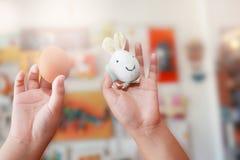 Huevo y conejo de Pascua en manos del niño Foto de archivo libre de regalías