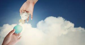 Huevo y conejo de Pascua en manos del niño contra el cielo azul Foto de archivo libre de regalías