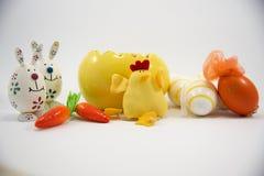 Huevo y pollo amarillos de Pascua con los pequeños huevos y zanahorias y conejitos decorativos Imagen de archivo